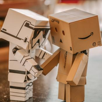Two robot-like figures, created from cardboard boxes, shake hands