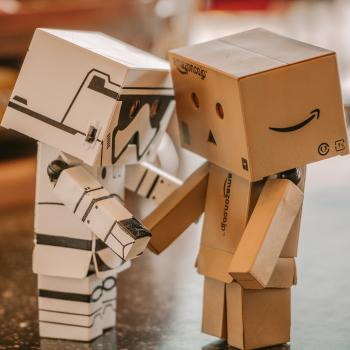 Two cardboard robots shake hands in agreement, having reached consensus.